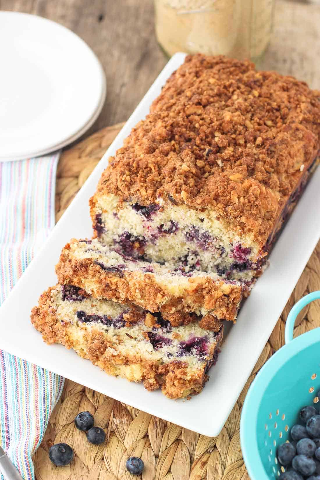 A loaf of half-sliced blueberry muffin bread on a rectangular tray.