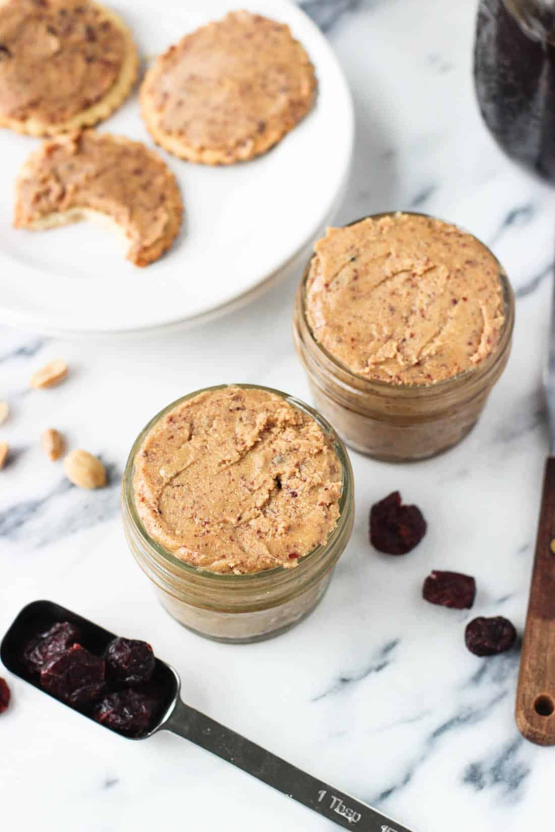 Two full jars of homemade peanut butters next to whole peanuts and dried cranberries.