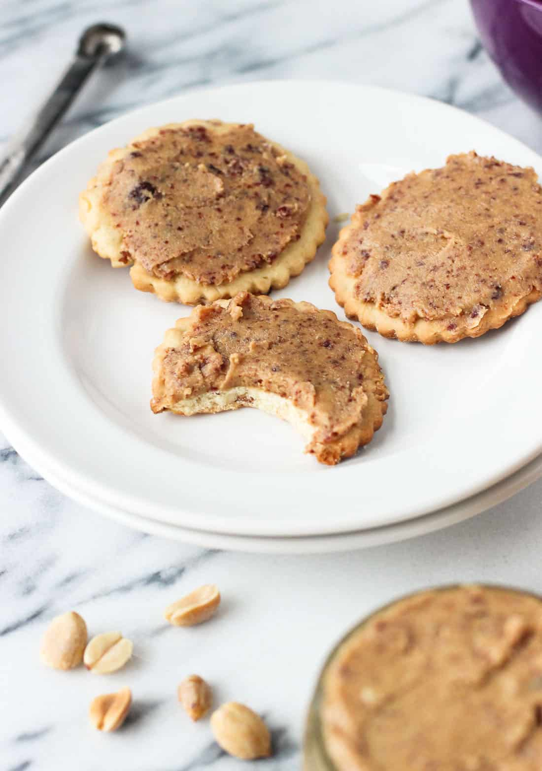 Homemade peanut butter spread on three crackers on a plate.