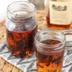 Two jars of vanilla extract: one with vanilla beans and one also with orange rind.