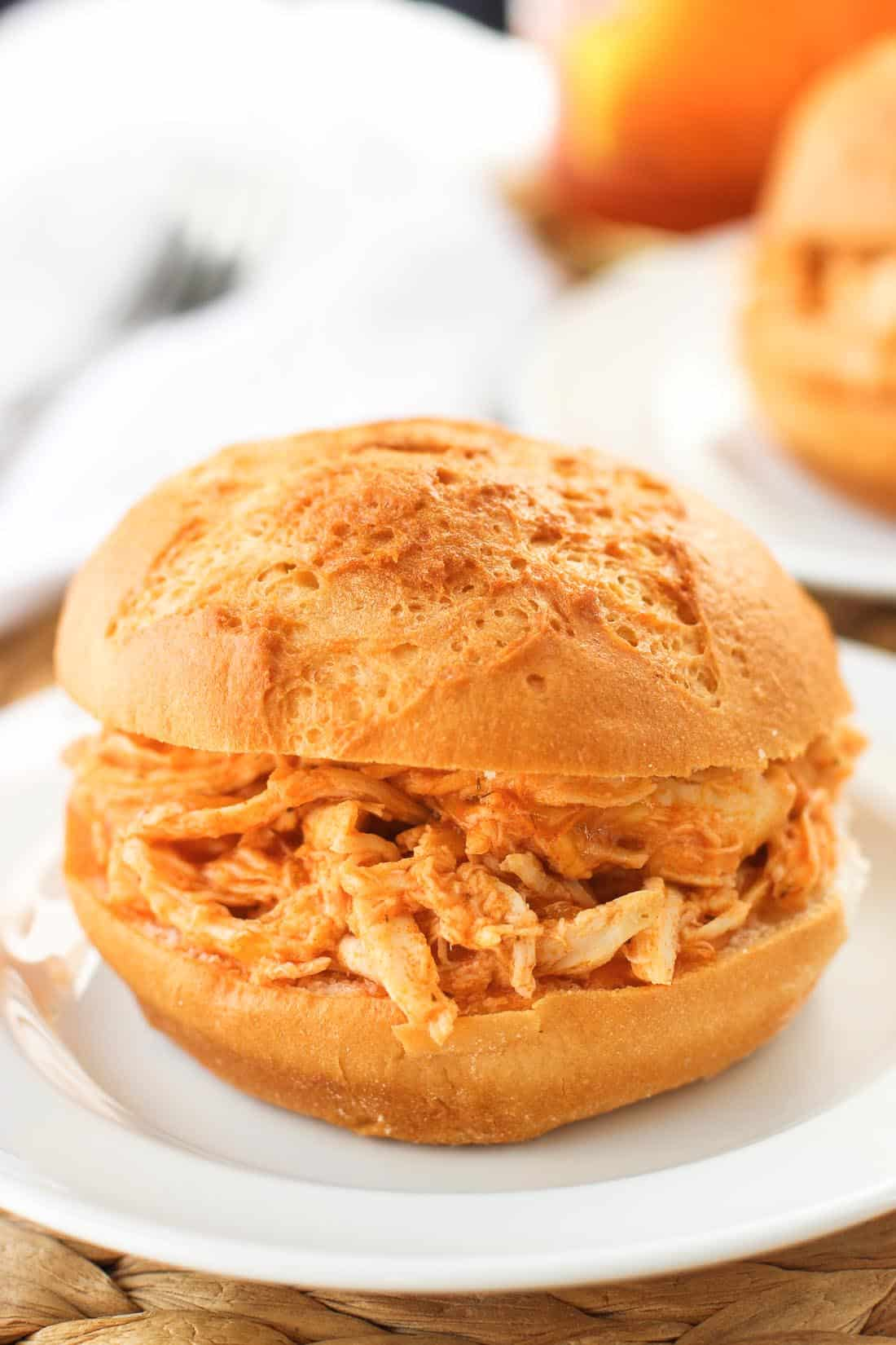 A buffalo chicken sandwich on a round roll.