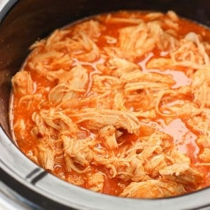 Shredded cooked chicken in buffalo sauce in a slow cooker.