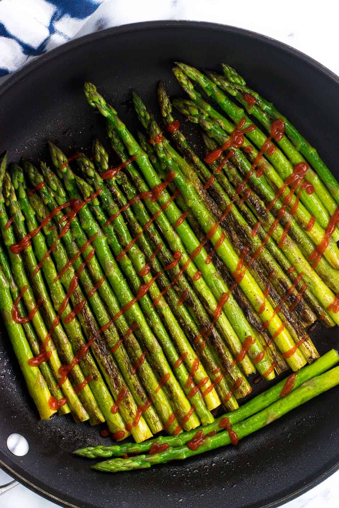 Asparagus in a large skillet drizzled with sriracha