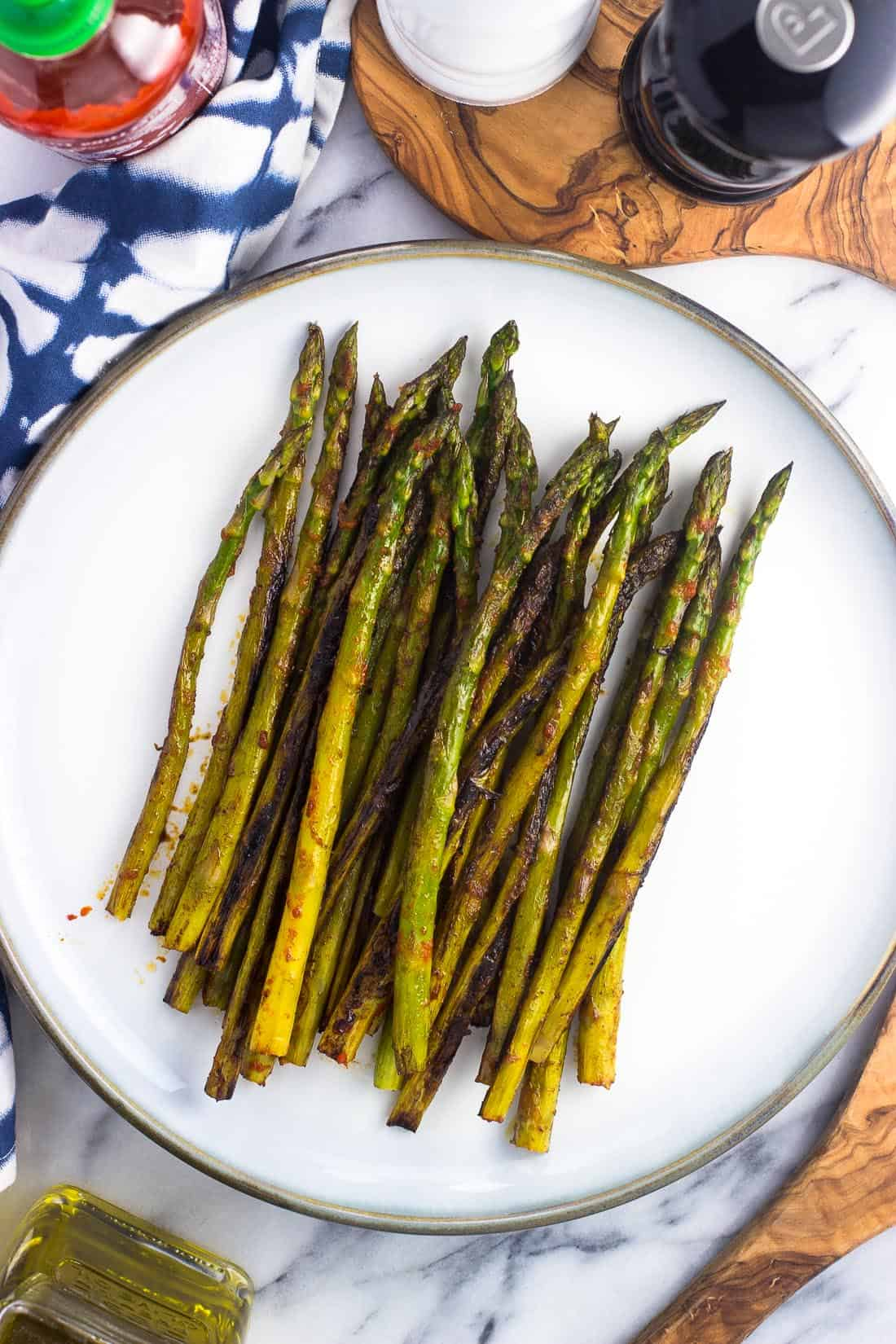 Sauteed asparagus roasted on the stovetop covered in a spicy sriracha mixture