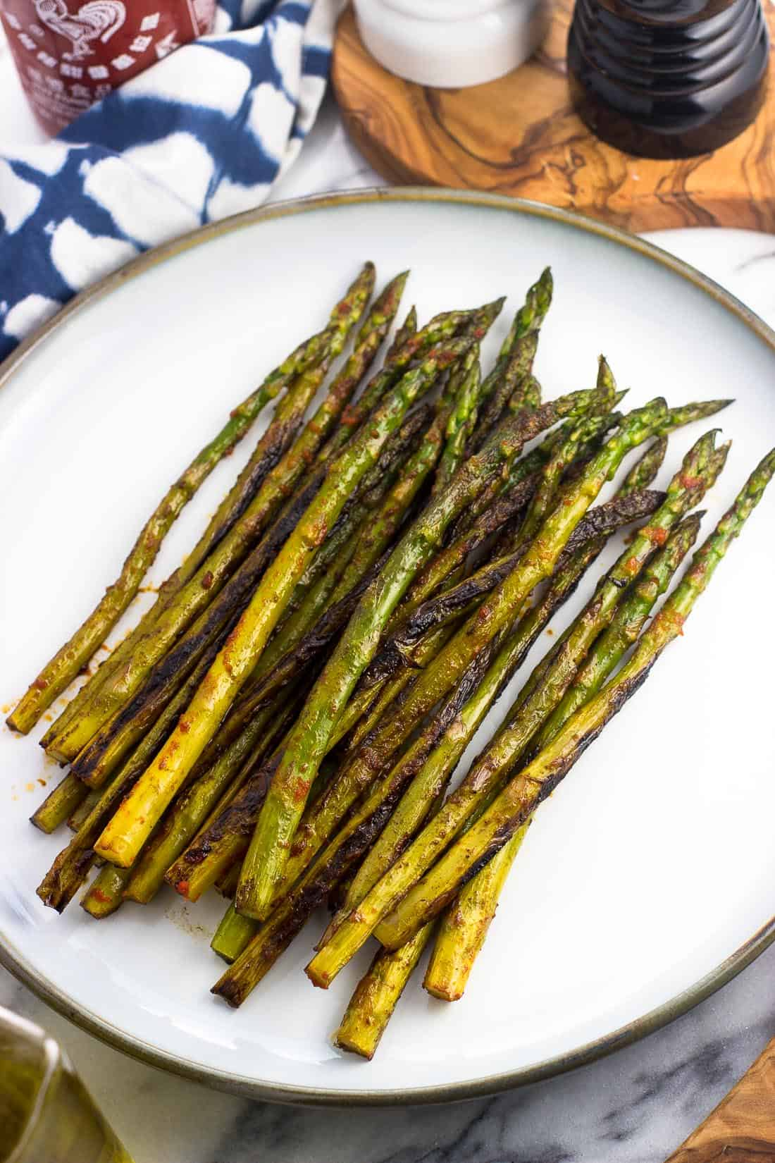 Sauteed asparagus on a serving plate after being roasted on the stovetop and seasoned with sriracha