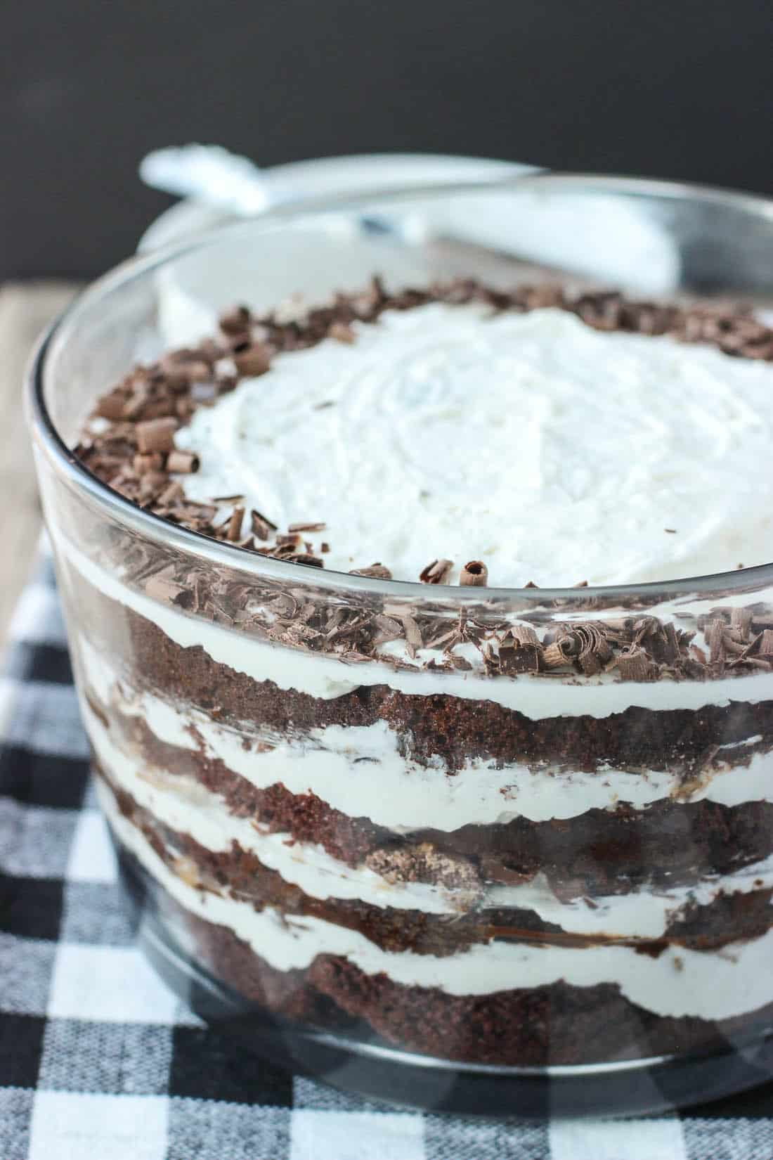 This chocolate toffee fudge trifle is a crowd-pleasing dessert at its finest! Layers of chocolate cake are topped with homemade whipped cream, hot fudge topping, and chocolate toffee pieces, and decorated with easy chocolate curls and festive holiday sprinkles. The whipped cream is stabilized so leftover portions stay well in the fridge for days!