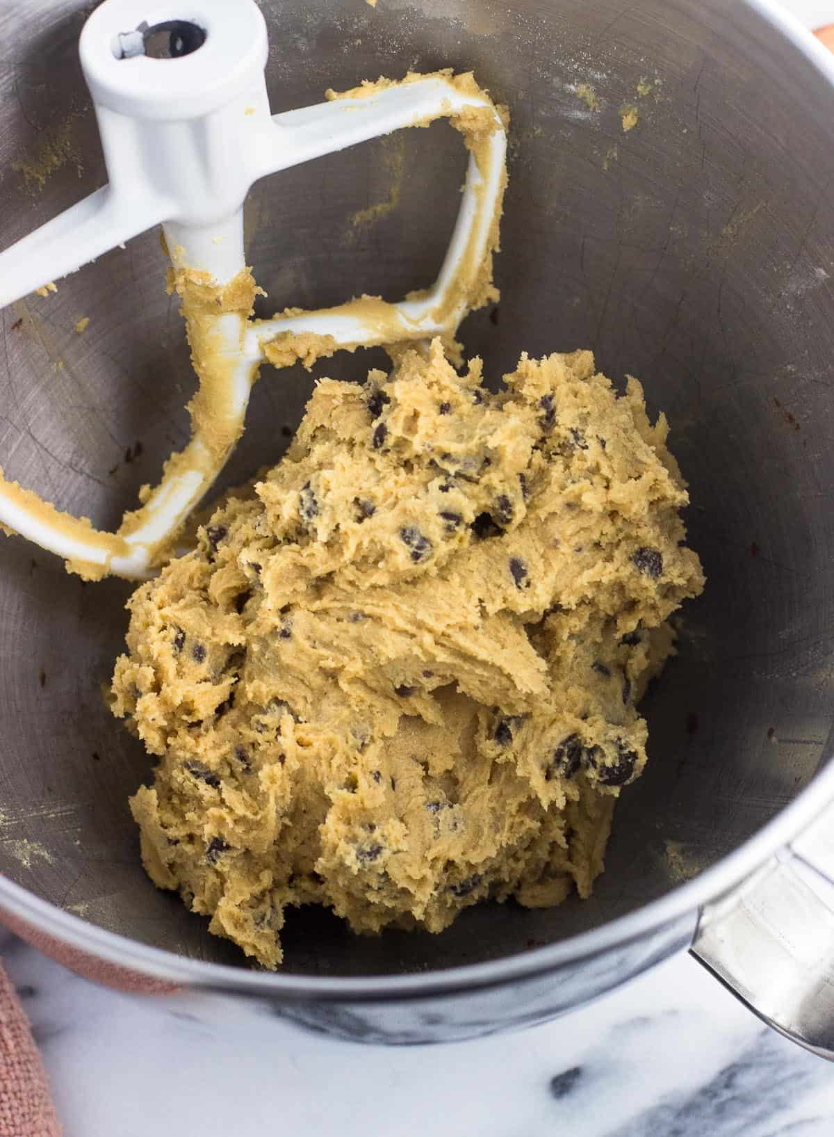 Chocolate chip cookie dough in a metal mixing bowl next to the stand mixer paddle attachment