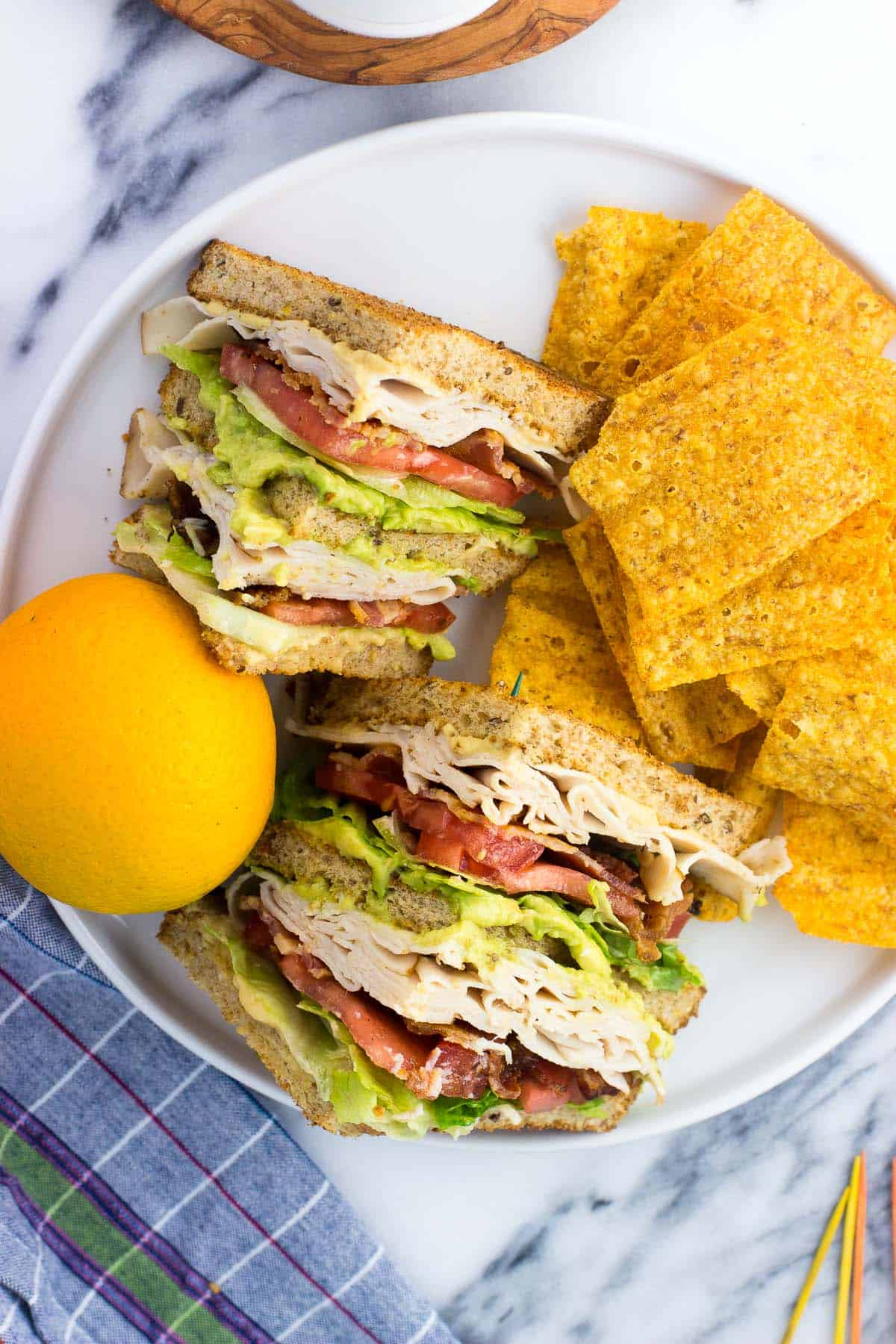 The sliced sandwich on a plate with an orange and chips.