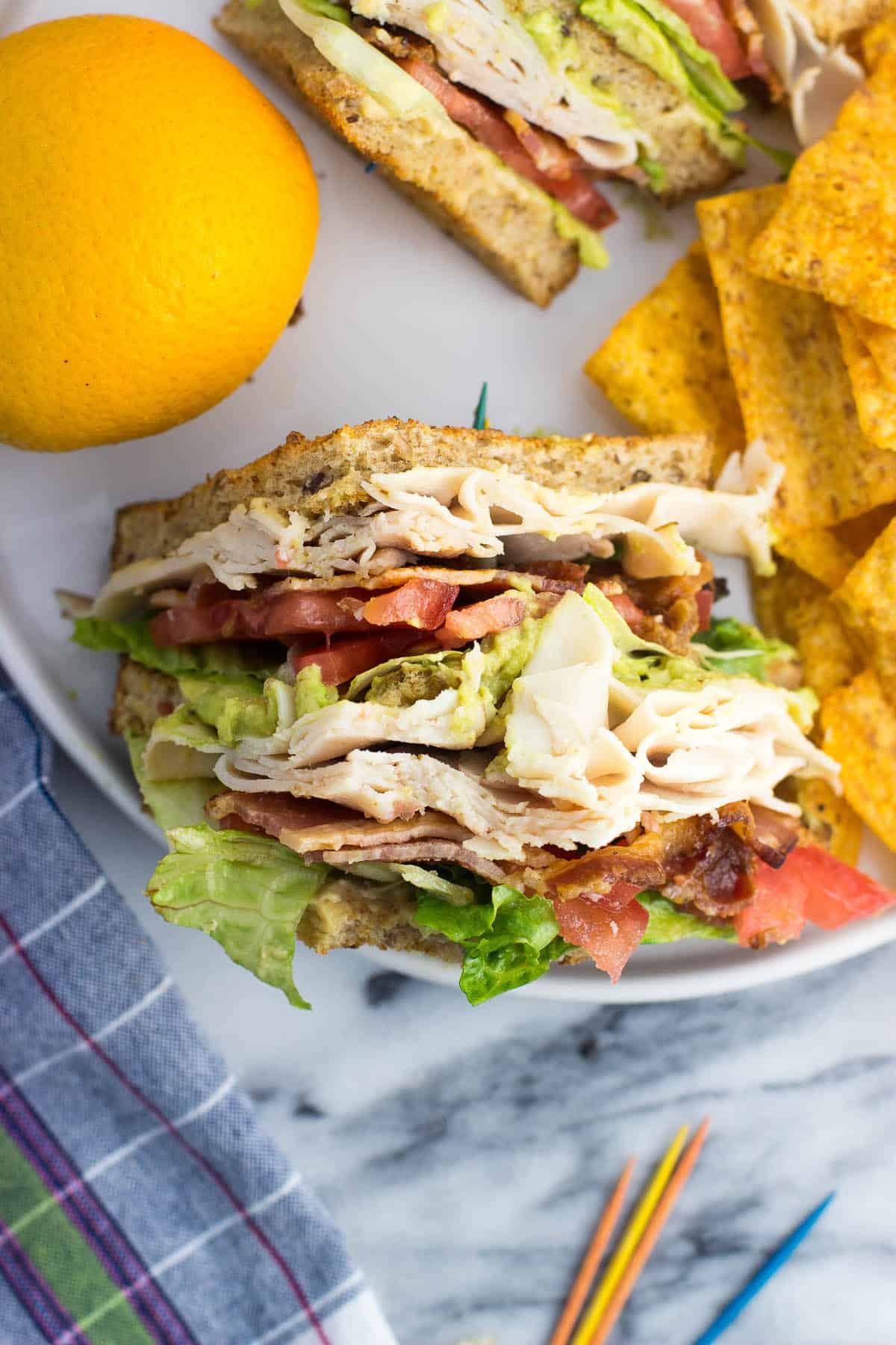 An overhead view of one sandwich half on a plate with chips and an orange.