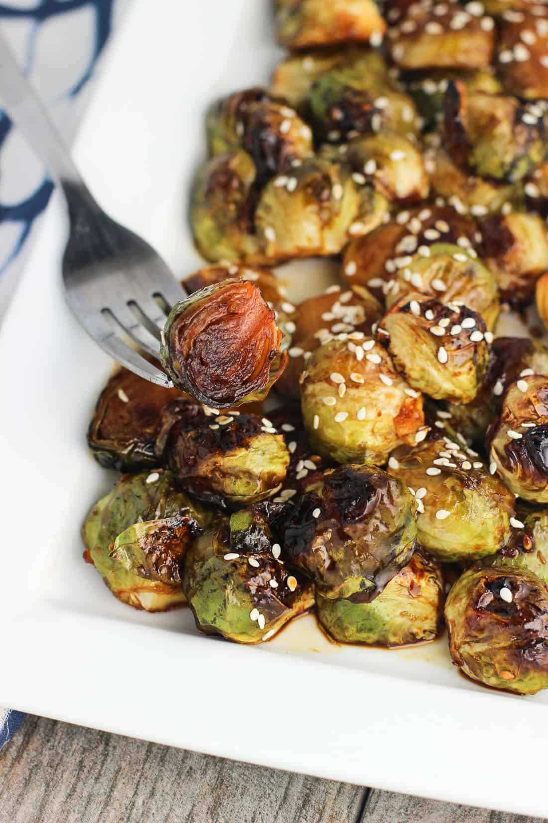A fork spearing a Brussels sprouts half from the tray showing the deeply roasted surface