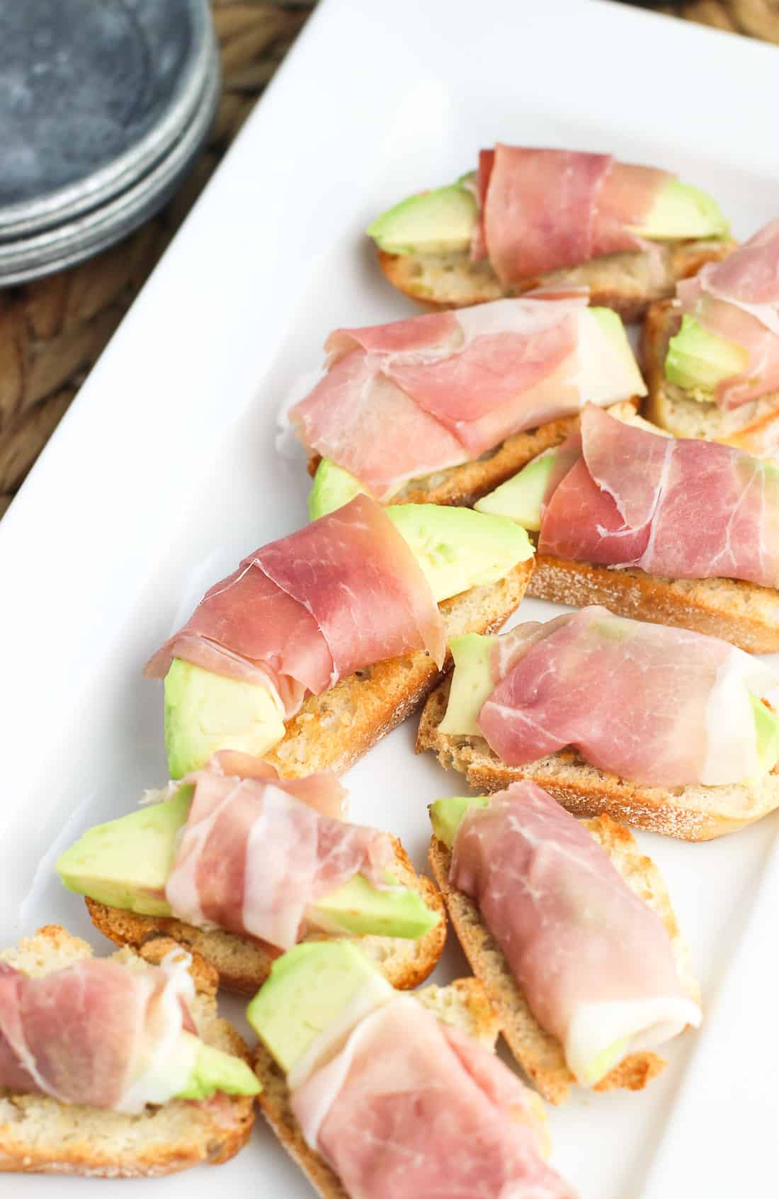 Prosciutto avocado crostini lined up on a serving tray before adding balsamic glaze.