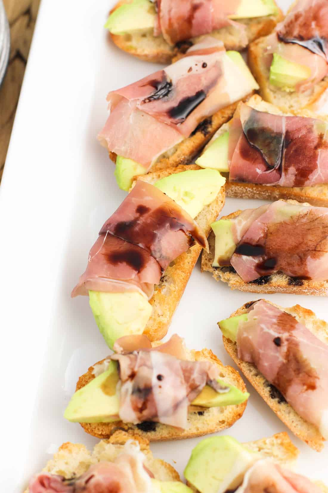 Prosciutto avocado crostini lined up on a serving tray.