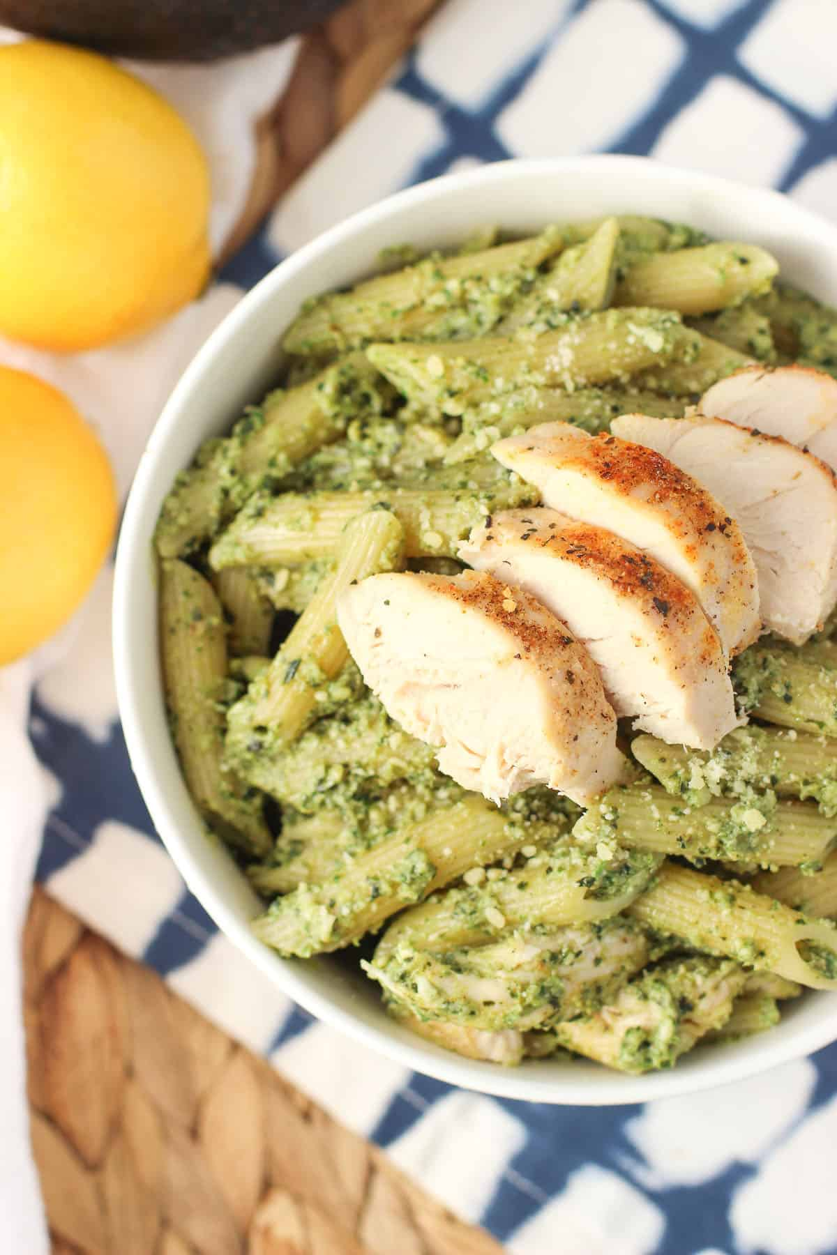 A bowl of pesto pasta with cooked chicken on top.