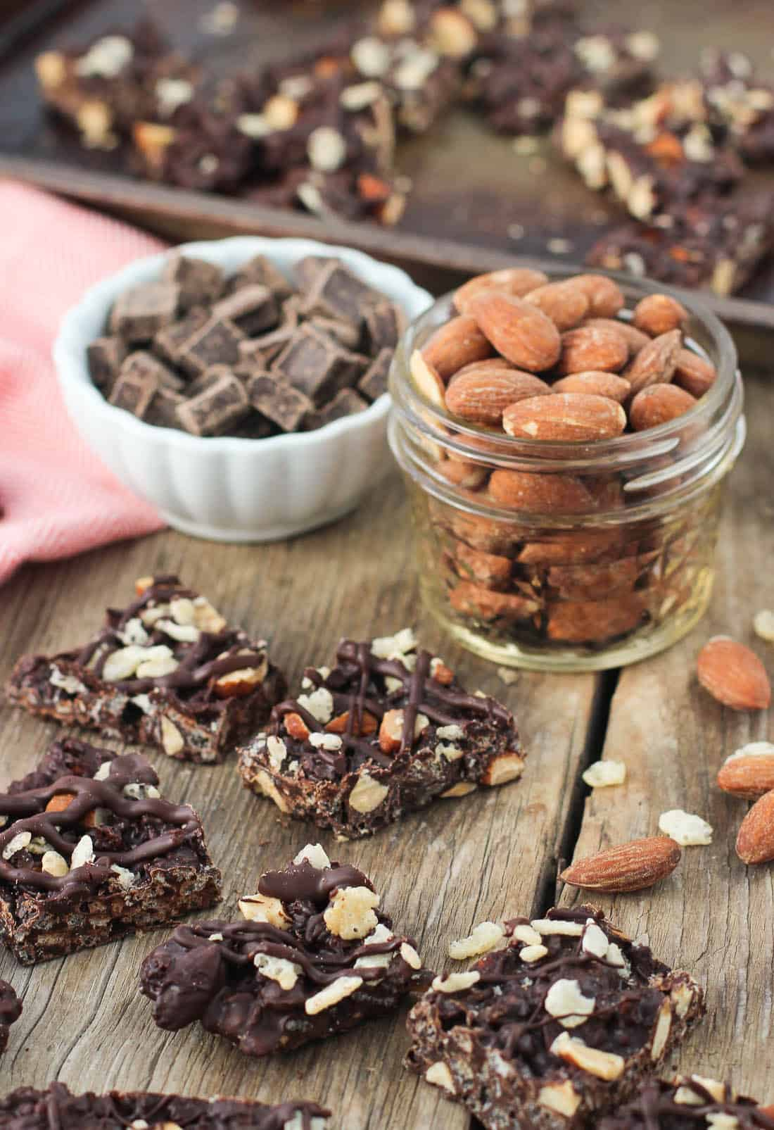 Chocolate bark pieces on a wooden table with jars of chocolate chunks and roasted almonds in the background