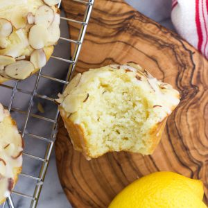 An overhead shot of a lemon ricotta muffin with a bite taken out of it on a small wooden serving board