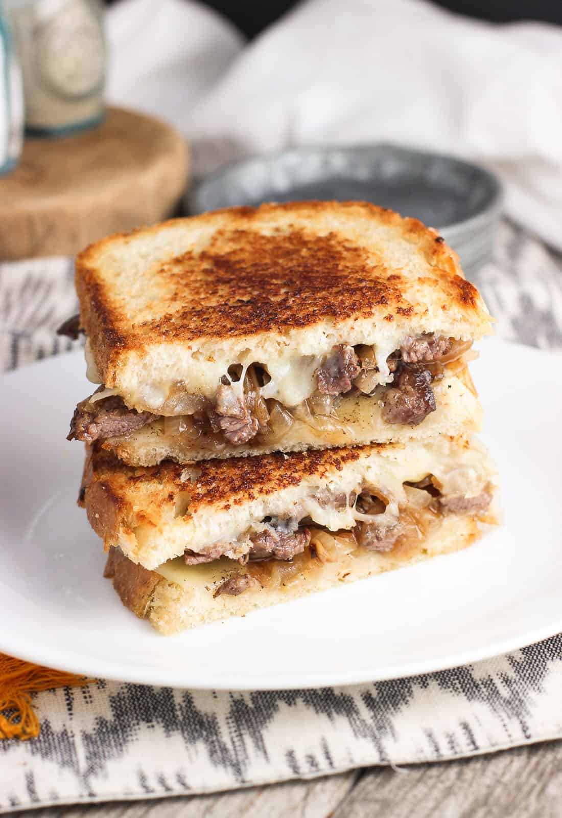 Two halves of a cheesesteak panini stacked on top of one another on a plate.
