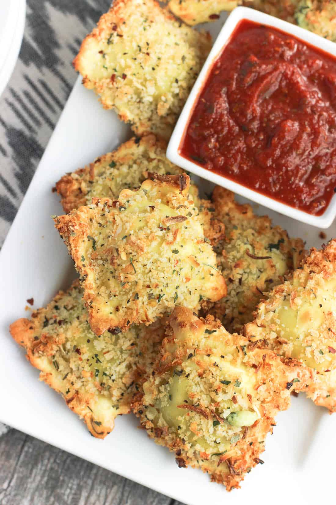 This easy recipe for crispy and baked toasted ravioli will be a new appetizer favorite! Ravioli is coated in egg and an Italian-spiced panko breadcrumb mixture and baked for a dish that's crisp and made-healthier! Serve with marinara sauce.