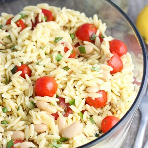 A large glass bowl of orzo pasta salad.