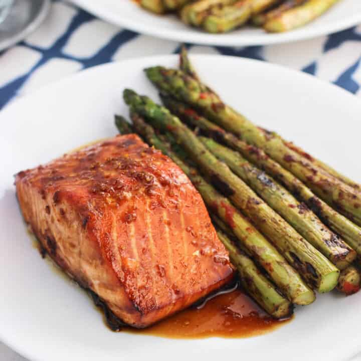 A salmon fillet, sauce, and asparagus on a plate.