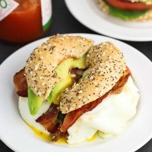 A BLT breakfast sandwich cut in half on a small plate.