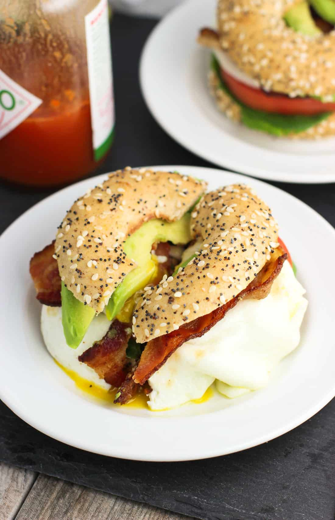 A BLT with avocado slices and egg on an everything bagel thin on a small plate next to a bottle of hot sauce
