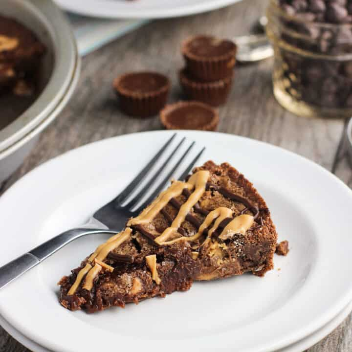 A rich and fudgy peanut butter brownie cake recipe that will feed a crowd! Peanut butter cups and chocolate and peanut butter chips are mixed into a chocolate and peanut butter brownie batter, baked, and topped with a fun PB + chocolate drizzle.