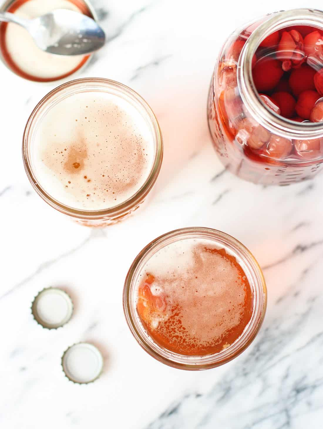 An overhead picture of two snakebites next to a big glass jar of maraschino cherries, a spoon, and two beer caps