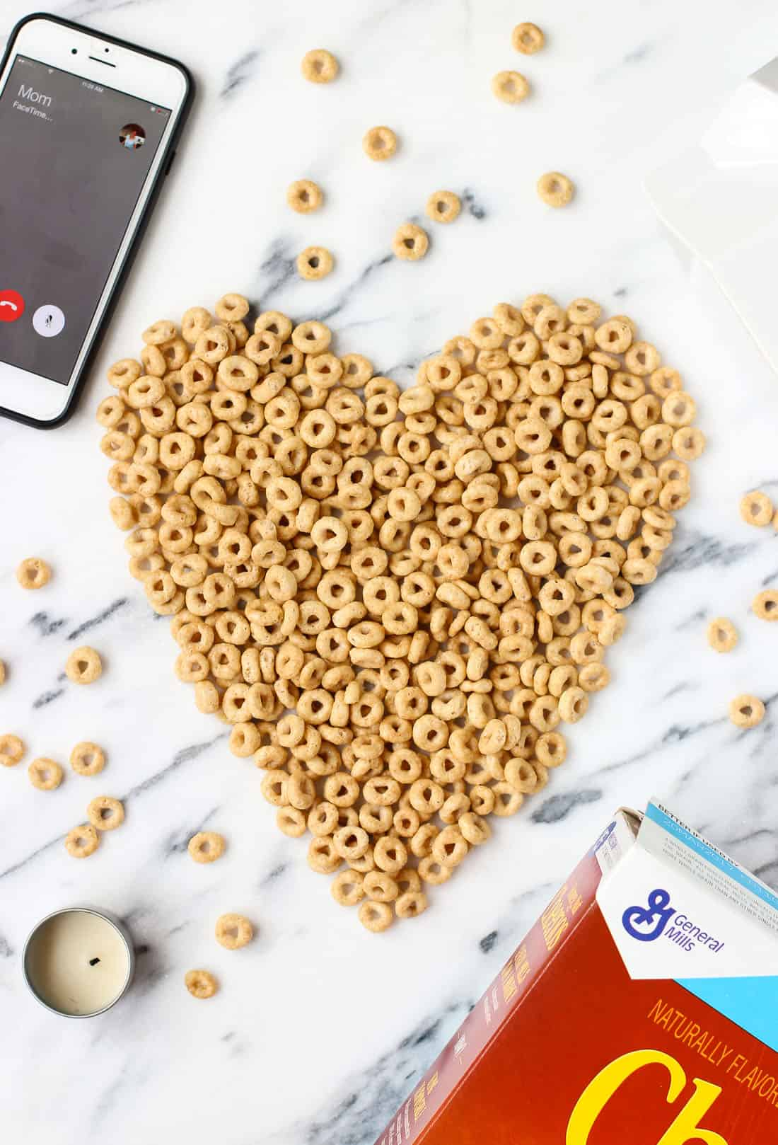 """Cheerios arranged into a heart shape on a marble board next to the box of cereal, a small tealight candle, and an iphone FaceTime calling the contact """"Mom"""""""