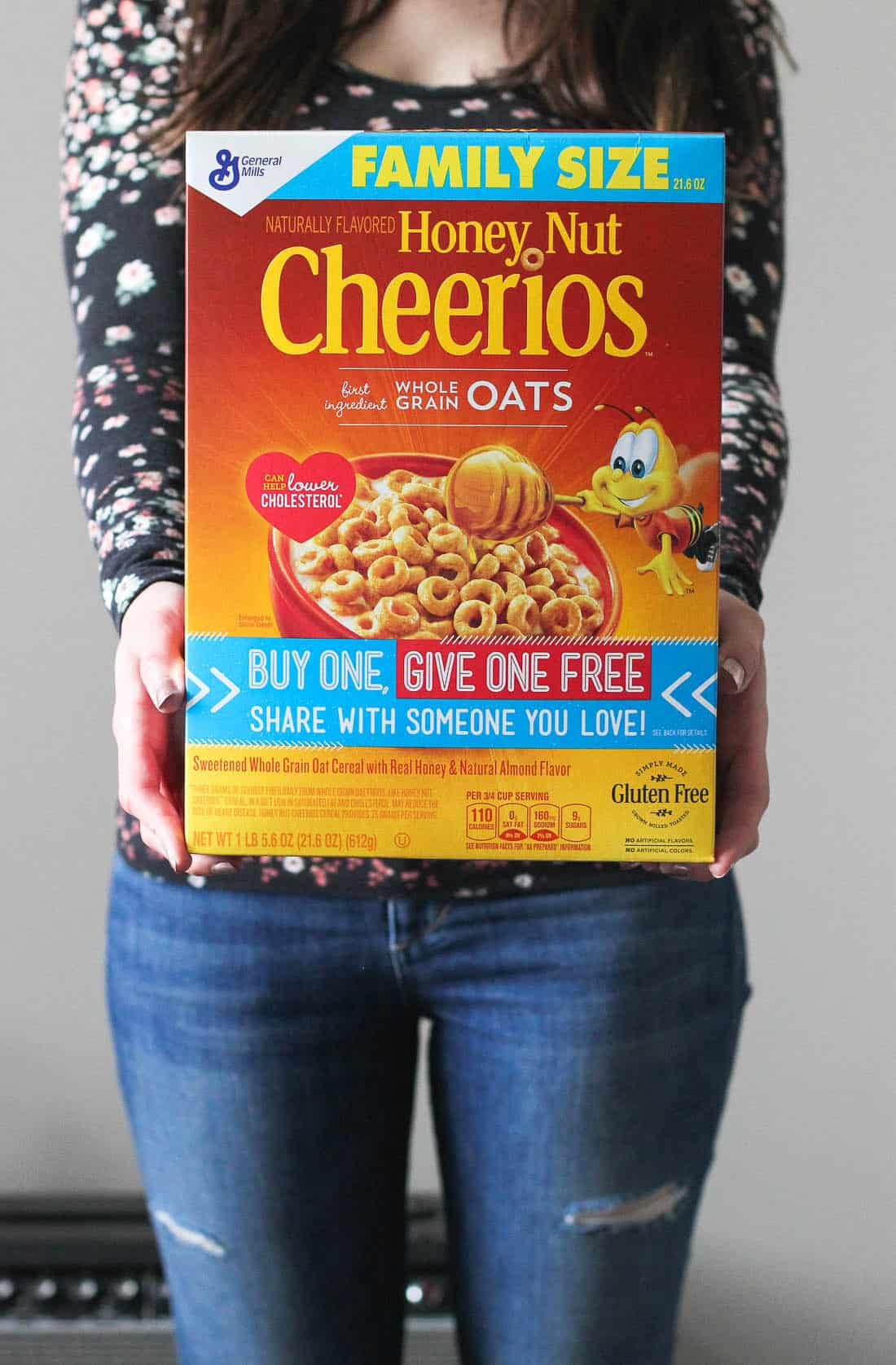 A woman holding a box of family size Honey Nut Cheerios in front of her