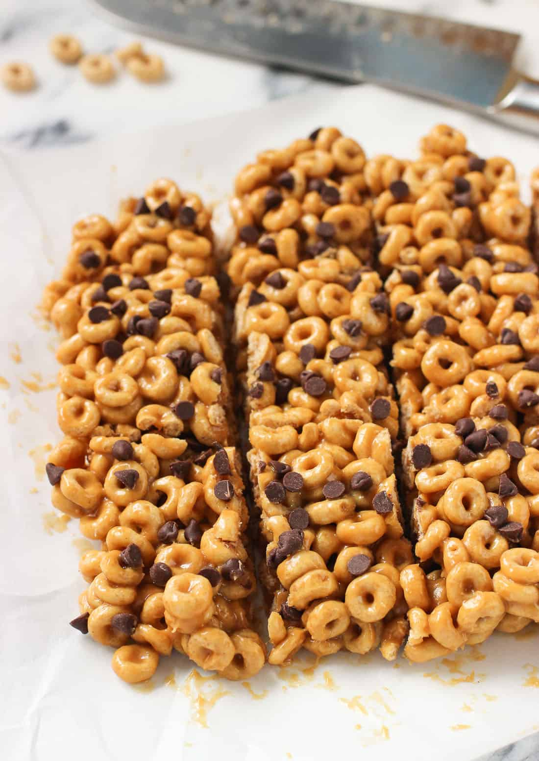 A slab of sliced cereal bars on a piece of parchment paper with a knife in the background