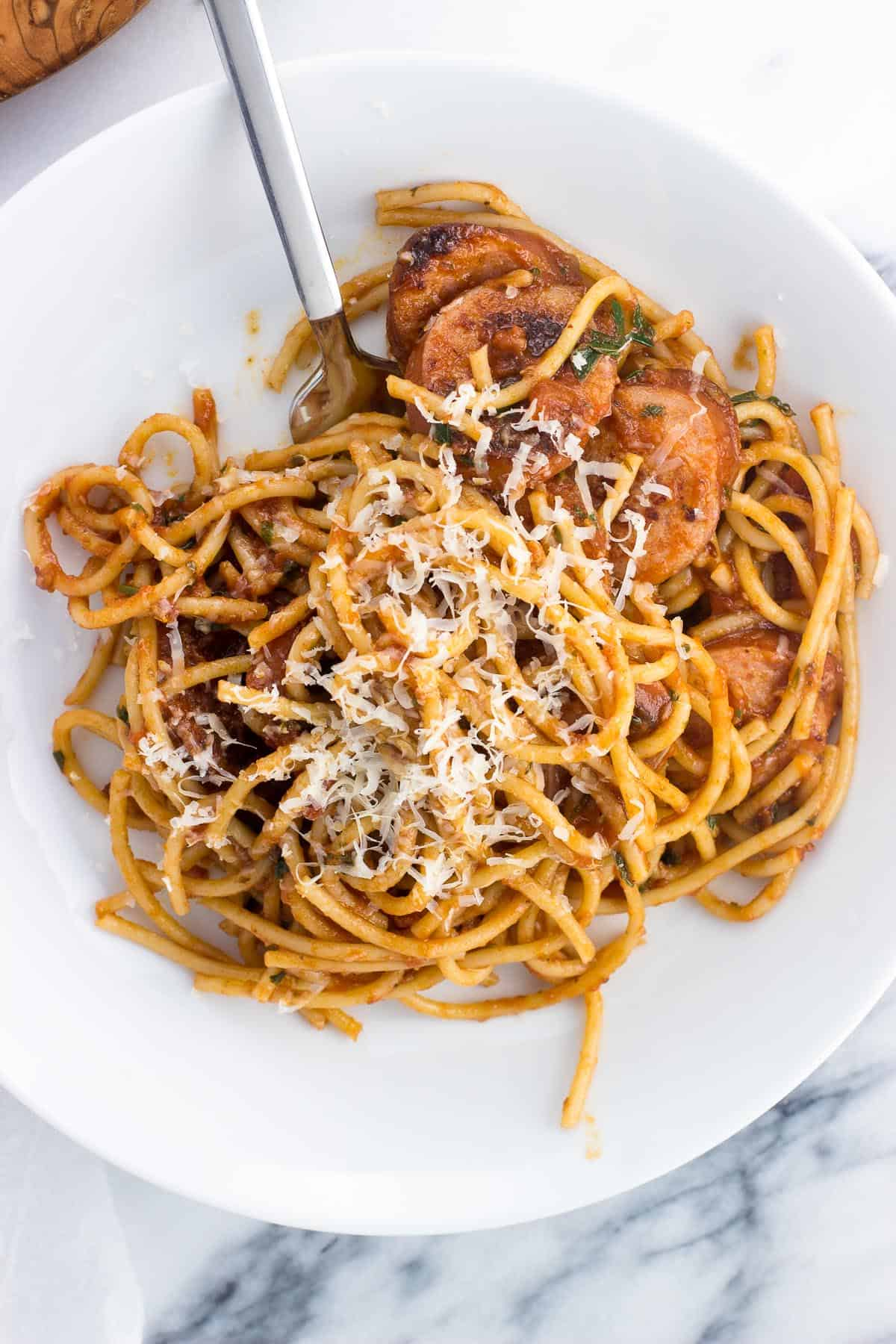 A ceramic pasta bowl of a portion of smoked sausage fra diavolo topped with grated Parmesan
