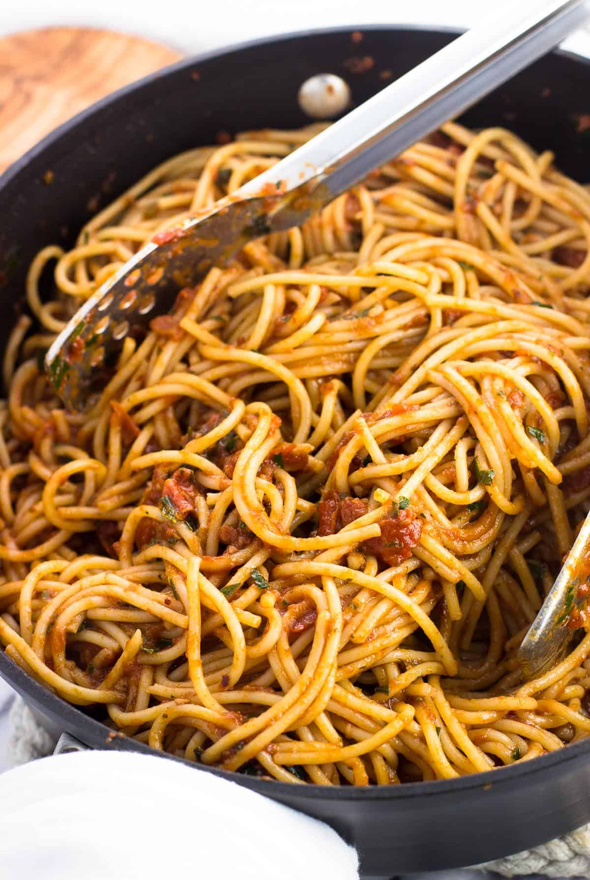 Spaghetti tossed in the sauce in a pan with a pair of tongs