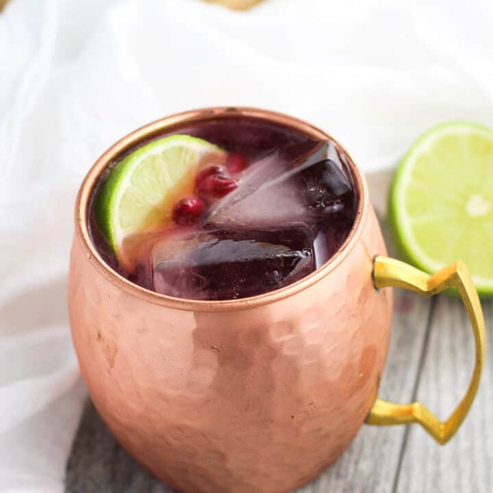 A pomegranate mule in a frosty hammered copper mug with two large square ice cubes, a lime wedge, and pomegranate arils