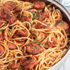 A pan full of spaghetti, fra diavolo sauce, and smoked sausage