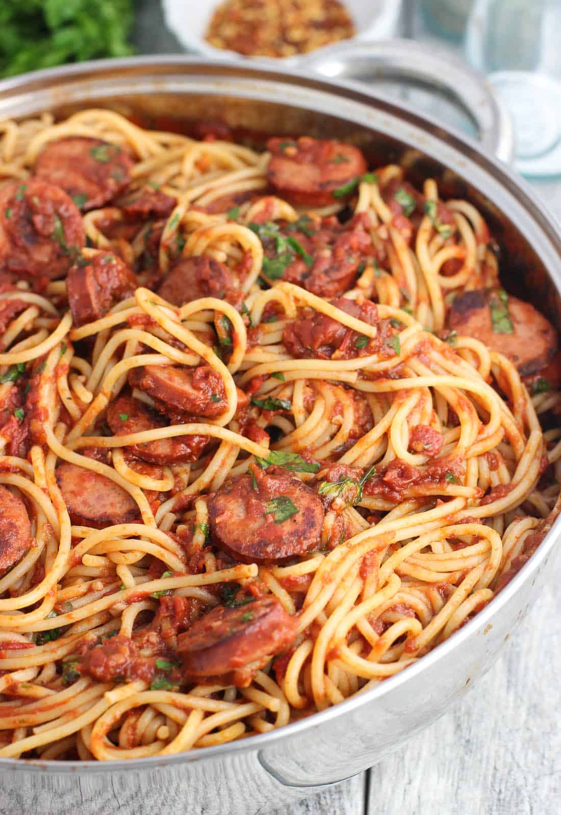 A large metal pan with taller sides filled with spaghetti, smoked sausage, and sauce ready to serve