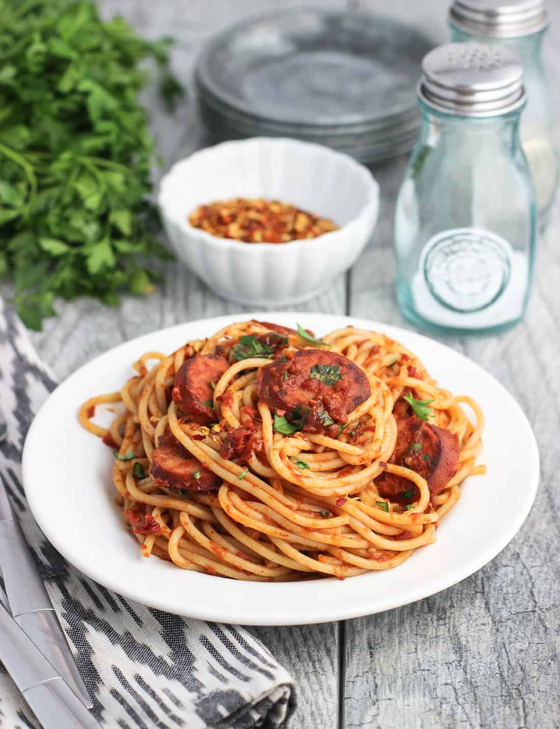 A serving of spaghetti fra diavolo with smoked sausage slices next to a bundle of fresh parsley, a bowl of crushed red pepper, and salt and pepper shakers