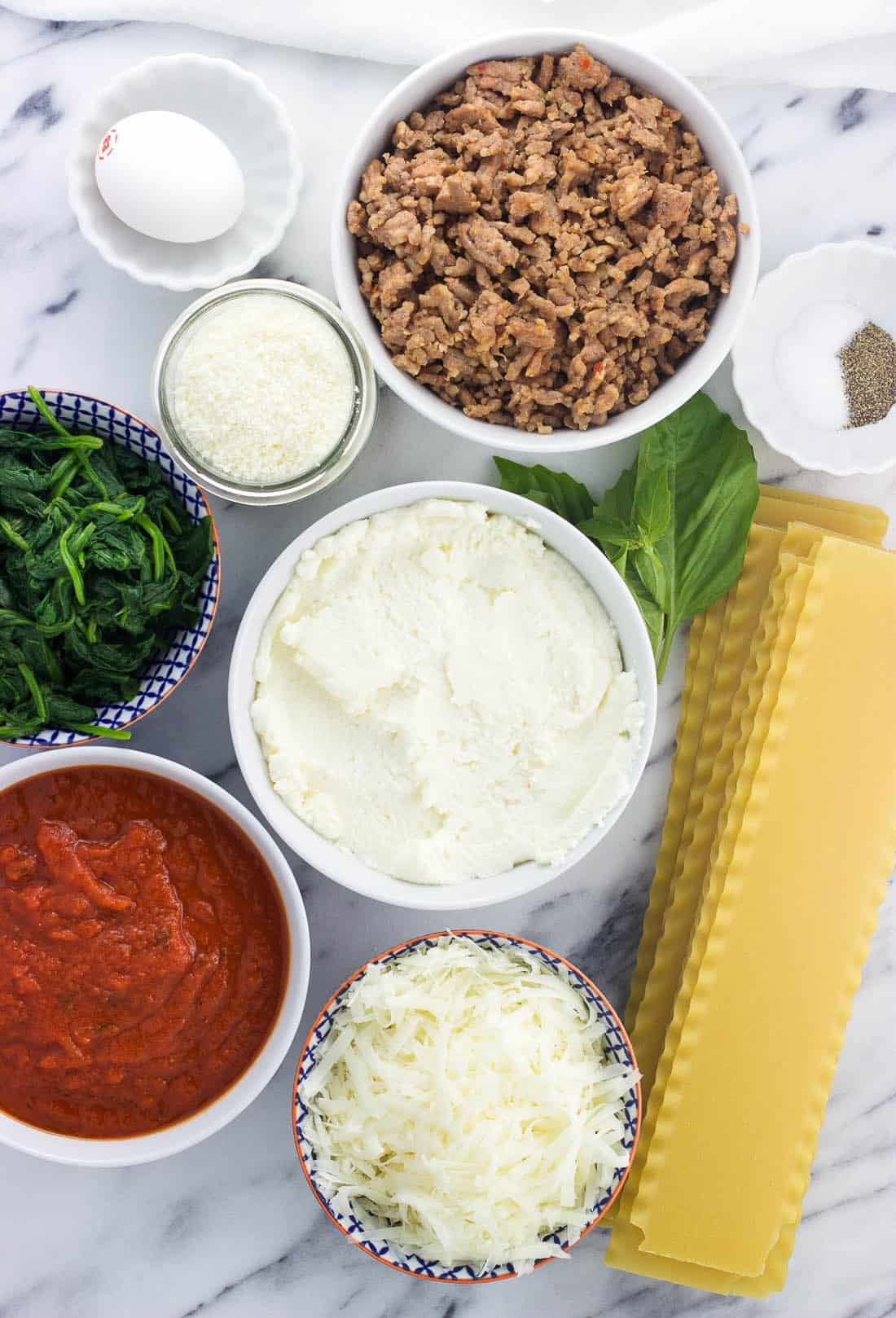 An overhead shot of lasagna roll ingredients in separate bowls
