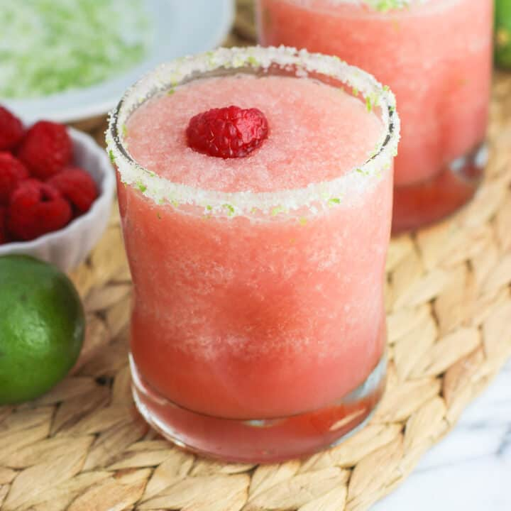 Two frozen blended margaritas garnished with salty lime rims and fresh raspberries.