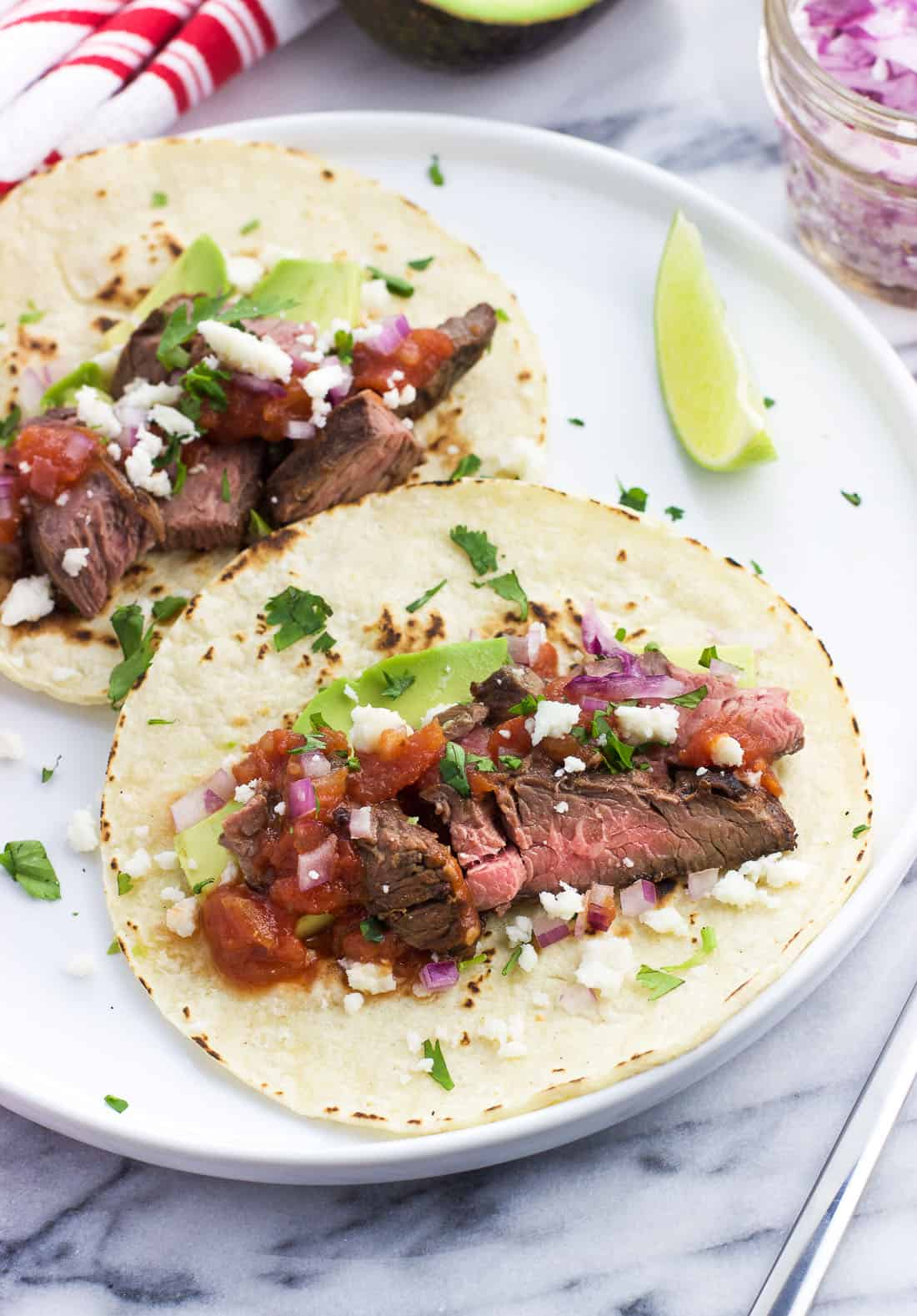 Grilled carne asada tacos on a white with a lime wedge and topped with chopped cilantro, crumbled cotija cheese, chopped red onion, avocado, and salsa.