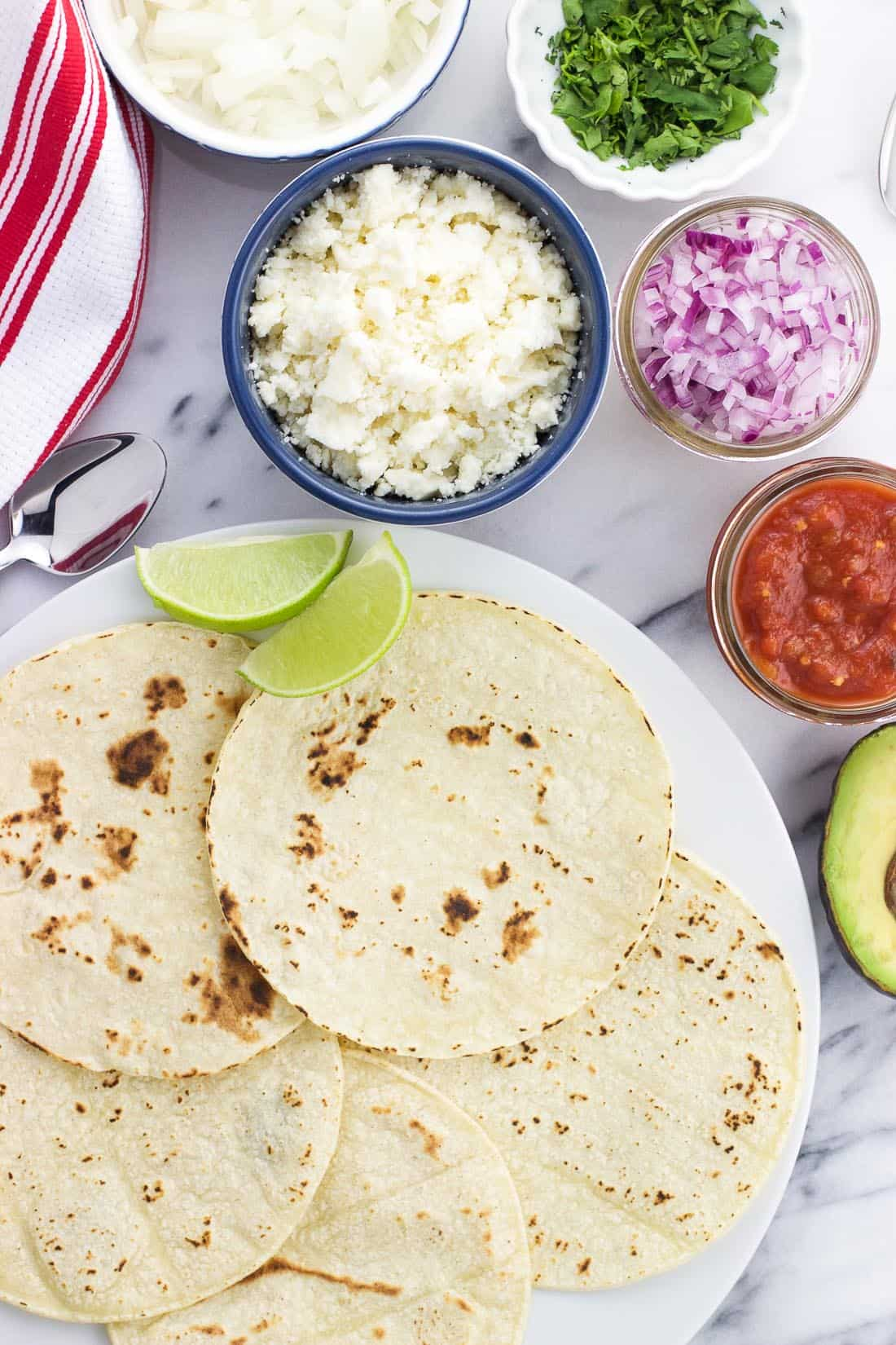 An overhead shot of all the taco fixings, including tortillas, cotija cheese, red onion, salsa, lime wedges, and avocado.