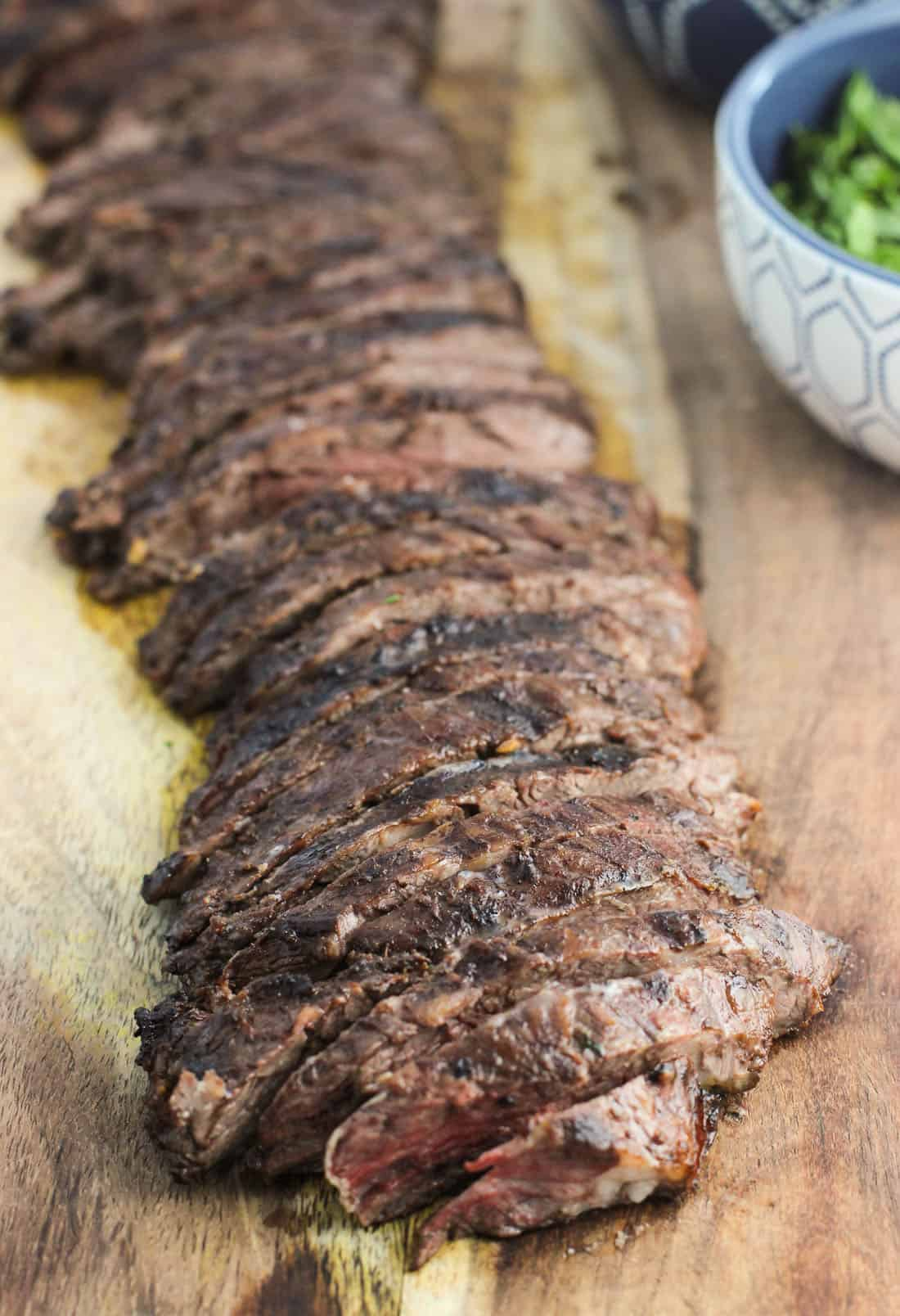 Grilled and sliced skirt steak on a wooden cutting board