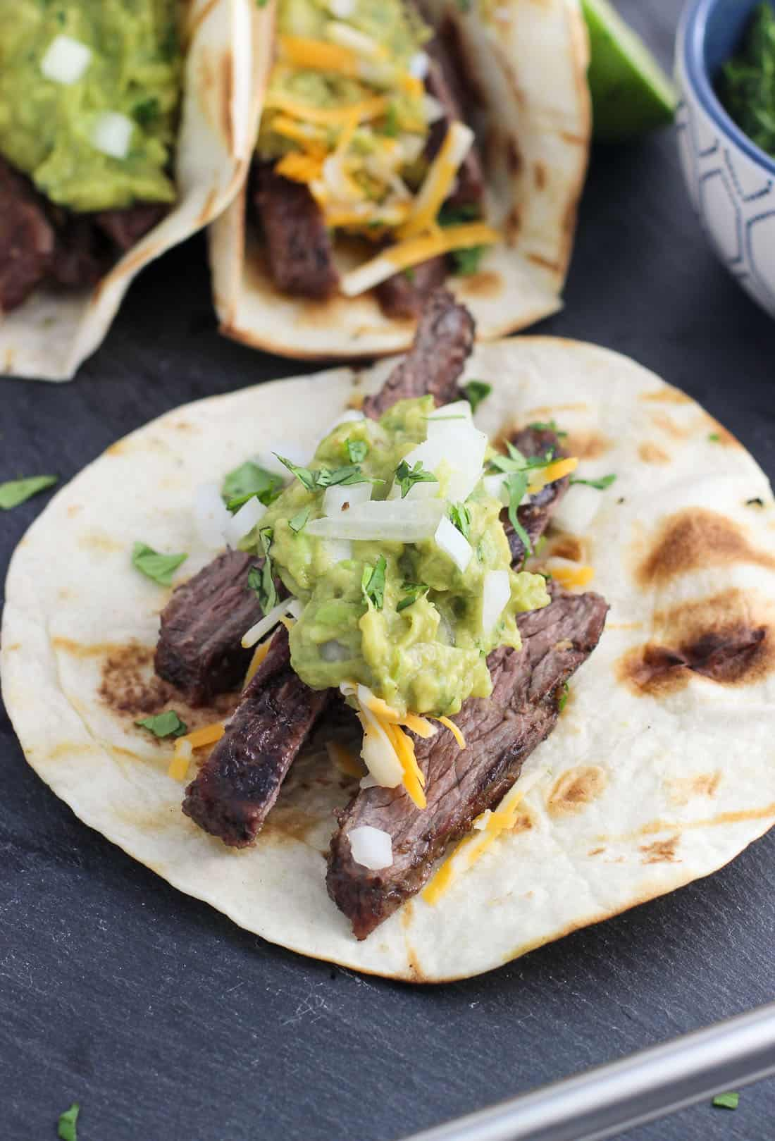 Carne asada tacos feature tender marinated + grilled skirt steak, grilled tortillas, and a plethora of your favorite taco toppings.