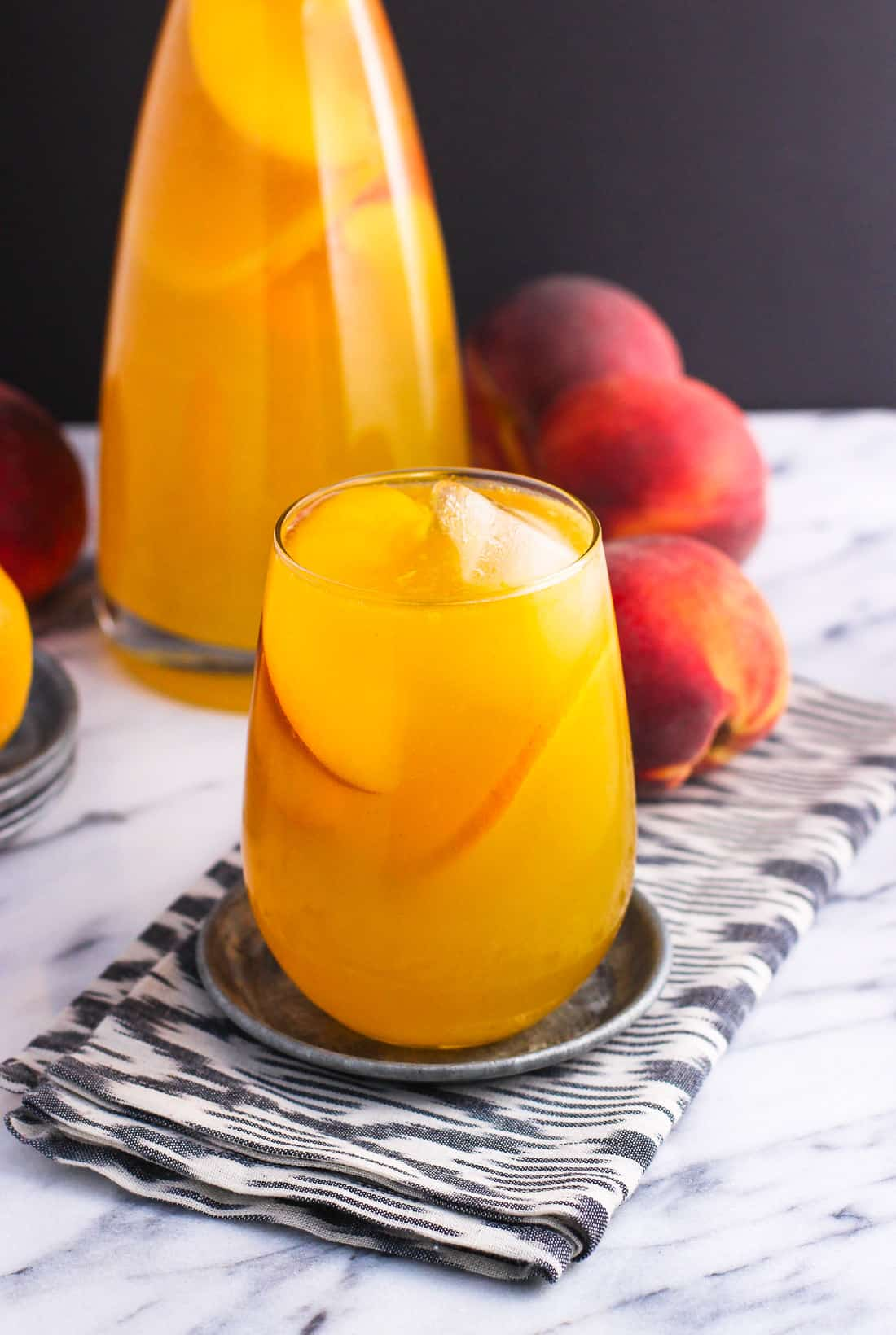 A glass of peach mango sangria garnished with ice cubes and peach slices in front of a carafe of sangria and peaches