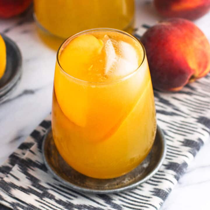 A glass of sangria garnished with ice cubes and peach slices on a metal coaster