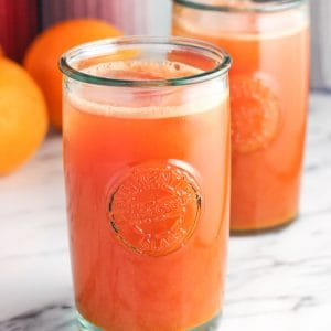Tall glasses of pressed juice on a table with fresh oranges.