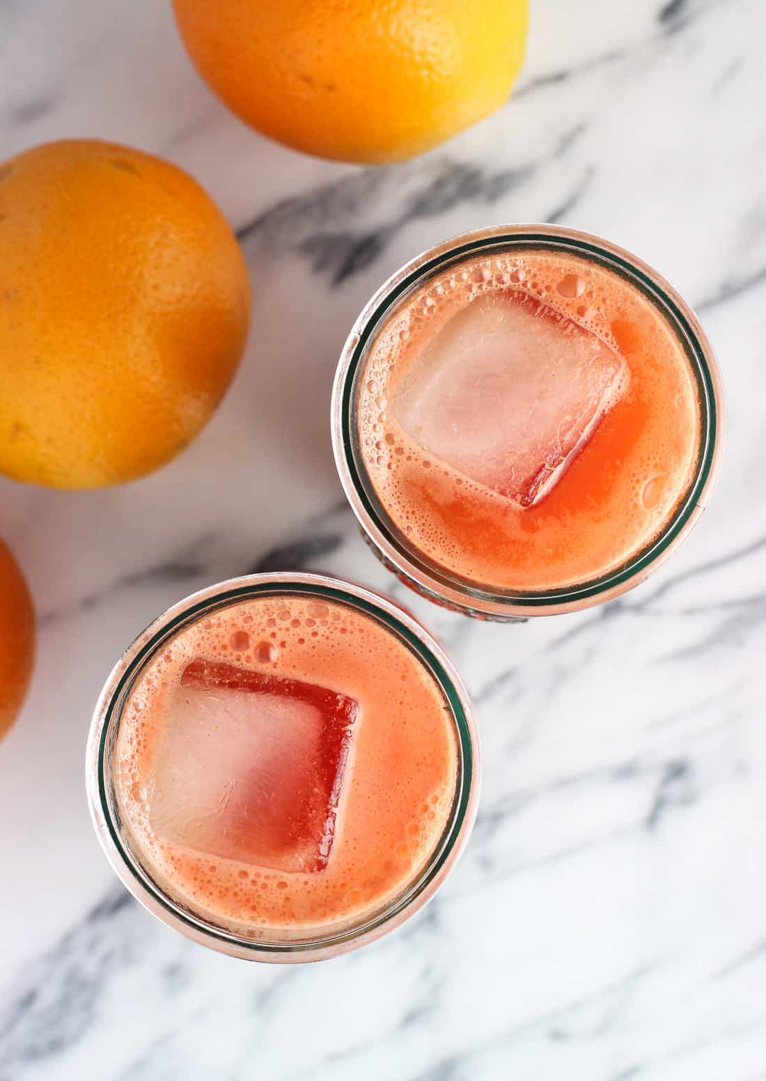 Big ice cubes floating in two glasses of juice.