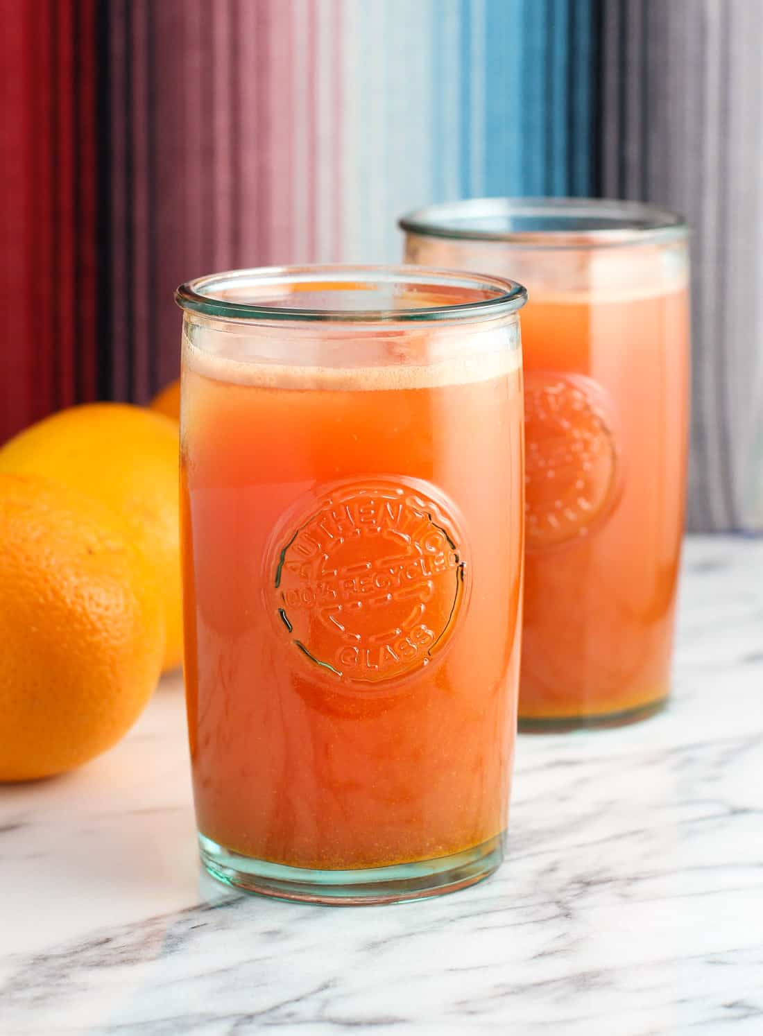 Glasses of juice with fresh oranges on a table.