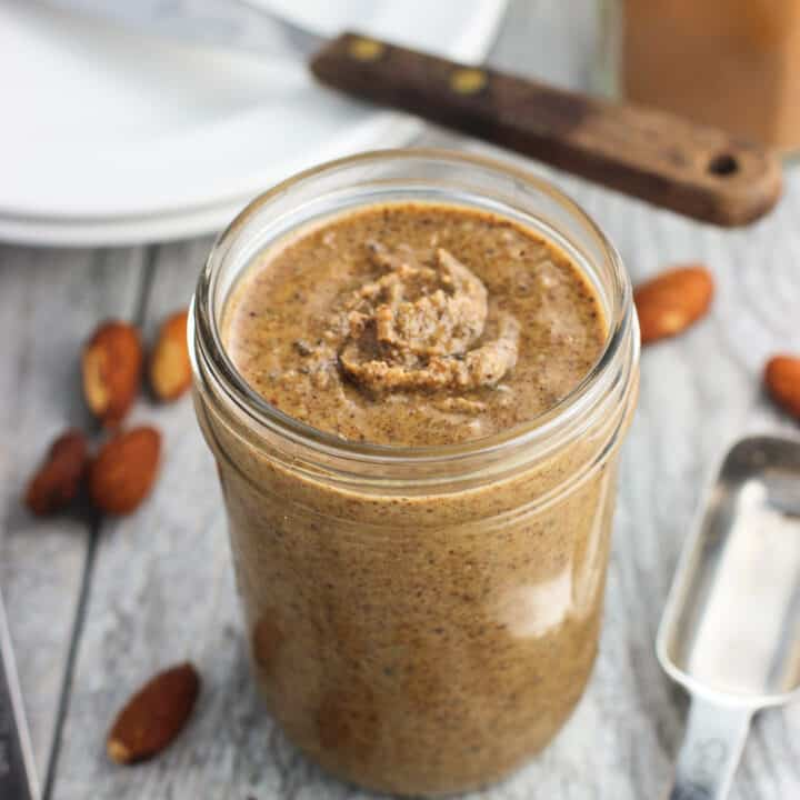 A clear glass jar of almond butter