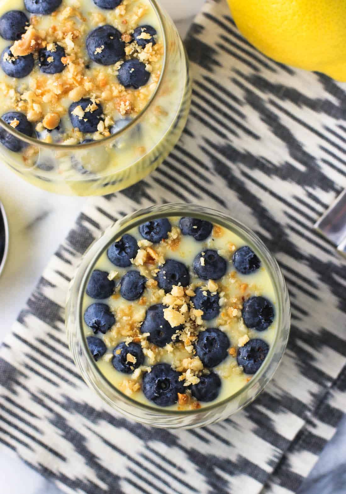 An overhead shot of two glasses filled with lemon pudding, topped with blueberries and nut crumble