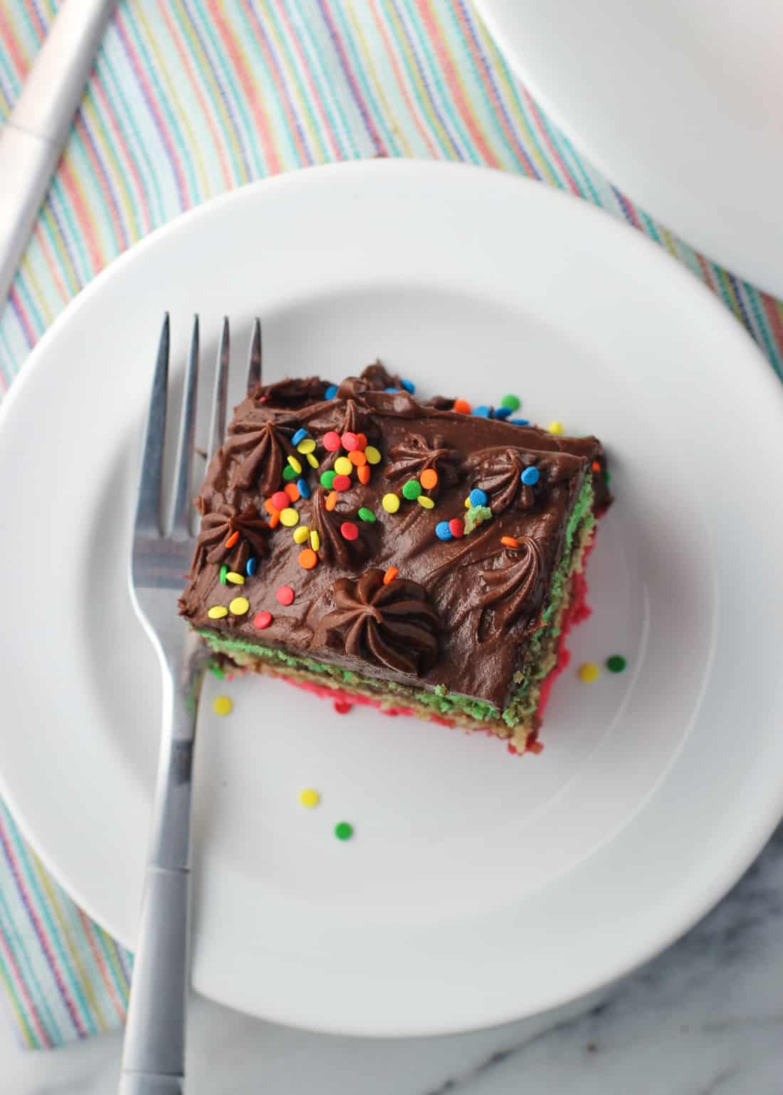 This rainbow cookie cake consists of three spongy, almond-flavored layers with chocolate raspberry frosting in between, and is topped with fluffy chocolate frosting. Each slice of this cake is like digging into one huge rainbow cookie - except with more chocolate!